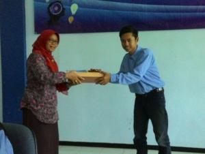 Penyerahan cindra mata yang di berikan oleh ketua pelaksana Ahmad Zidni Mubarok kepada ibu Anik Kusmiati selaku dosen pembina dalam acara KIM di Gedung AE lantai 2.