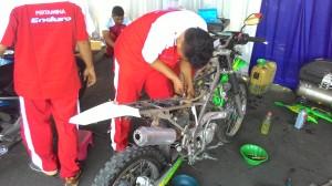 Salah satu mekanik dari Jurusan Teknik Mesin sedang memperbaiki sepeda motor milik peserta servis gratis.